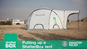 ShelterBox tent pitched in a field with Rotary logo